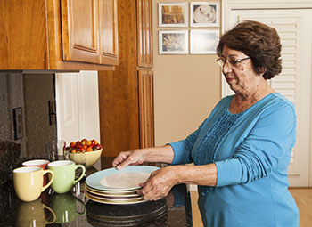 Woman at the kitchen counter lifting a clean plate.