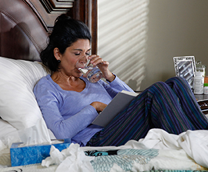 Woman at home, sick in bed.