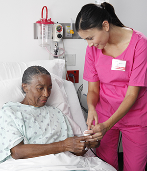 Healthcare provider showing PCA pump button to woman lying in hospital bed.
